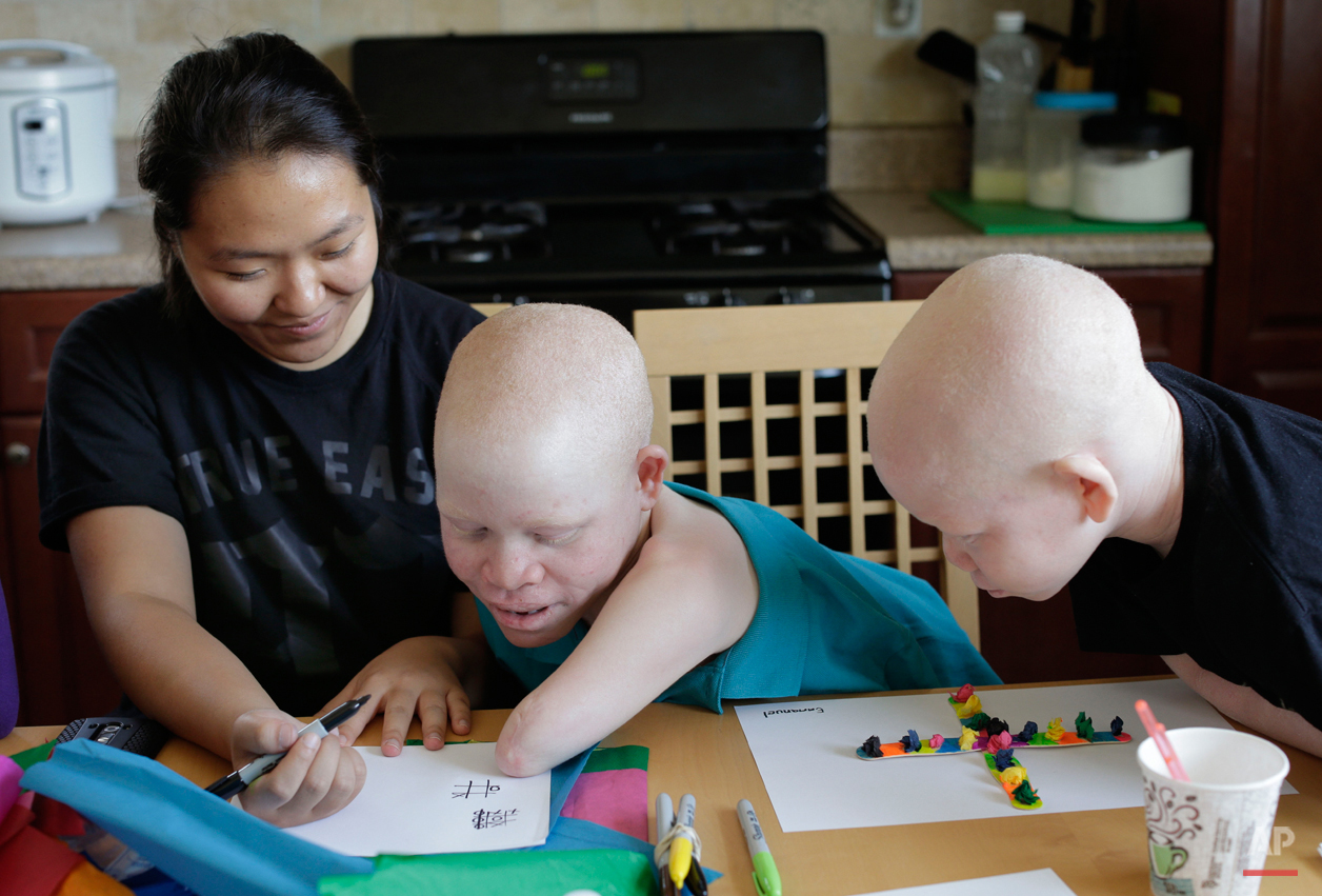 Emmanuel Rutema plays Tic-Tac-Toe with Mwigulu Magesa and tutor June Chung in New York on Tuesday, July 28, 2015. The children were attacked and dismembered in Tanzania because of a belief that their body parts will bring wealth.  (AP Photo/Julie Jacobson)