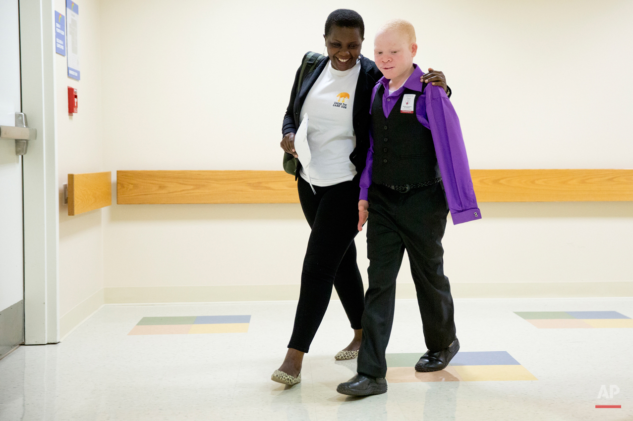 Emmanuel Rutema, 13, of Tanzania, walks with interpreter Ester Rwela before his surgery at the Shriners Hospital for Children in Philadelphia on Tuesday, June 30, 2015. Rutema and four other children also with albinism are in the U.S. to receive free surgery and prostheses at the hospital. One out of every 1,400 citizens in Tanzania has albinism. (AP Photo/Matt Rourke)