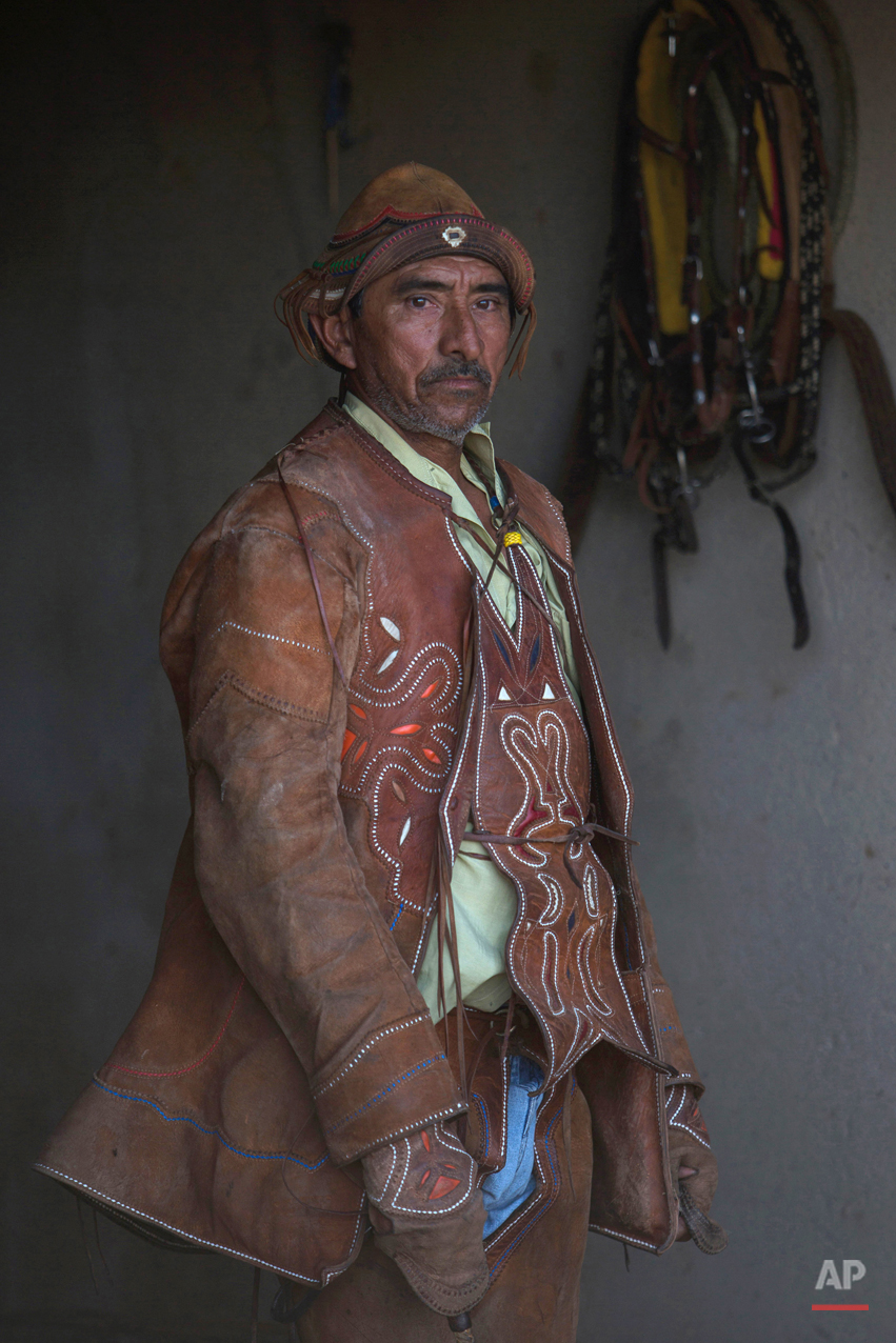 """In this July 24, 2015 photo, Joao de Cazuza wears his """"gibao"""" cowboy suit as he gets ready to compete in the annual Catch the Bull competition known as """"Pega do Boi"""" in Serrita, in Brazil's Pernambuco state. The 56-year-old said he was just 15 when donned his first traditional riding outfit, and ìfrom that moment on I knew I was a """"vaqueiro.î (AP Photo/Eraldo Peres)"""
