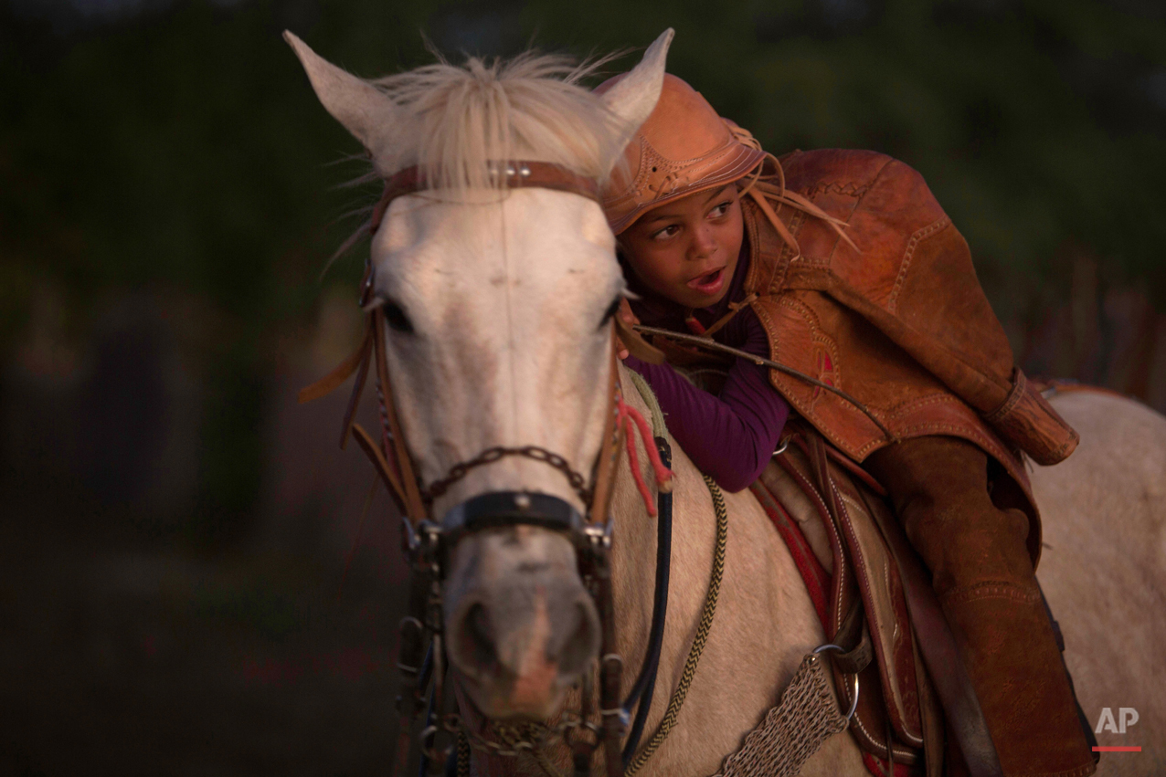 """In this July 24, 2015 photo, 7-year-old Garoto Ozeas rests on his horse after watching the annual Catch the Bull competition known as the """"Pega do Boi"""" in Serrita, in Brazil's Pernambuco state. There's no minimum age to compete, but the youngest riders are about 17-years-old. (AP Photo/Eraldo Peres)"""