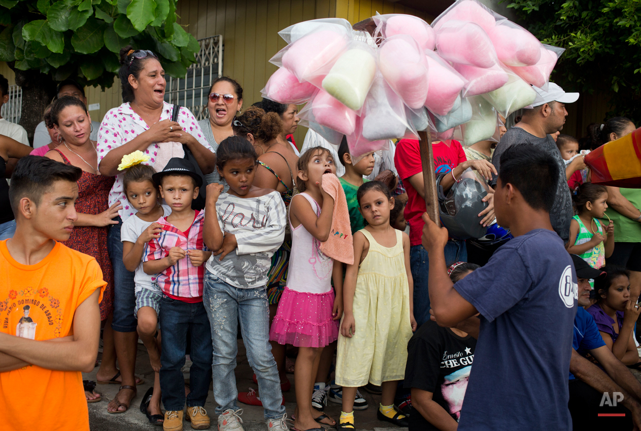 In this Aug. 7, 2015 photo, a girl makes a face as she reacts to cotton candy for sale during Managua's patron saint, Santo Domingo de Guzman's celebration, in Managua, Nicaragua. Outside the Santo Domingo Las Sierritas parish vendors hawk all kinds of religious items, carnival food, games of chance, toys and popular art. (AP Photo/Esteban Felix)