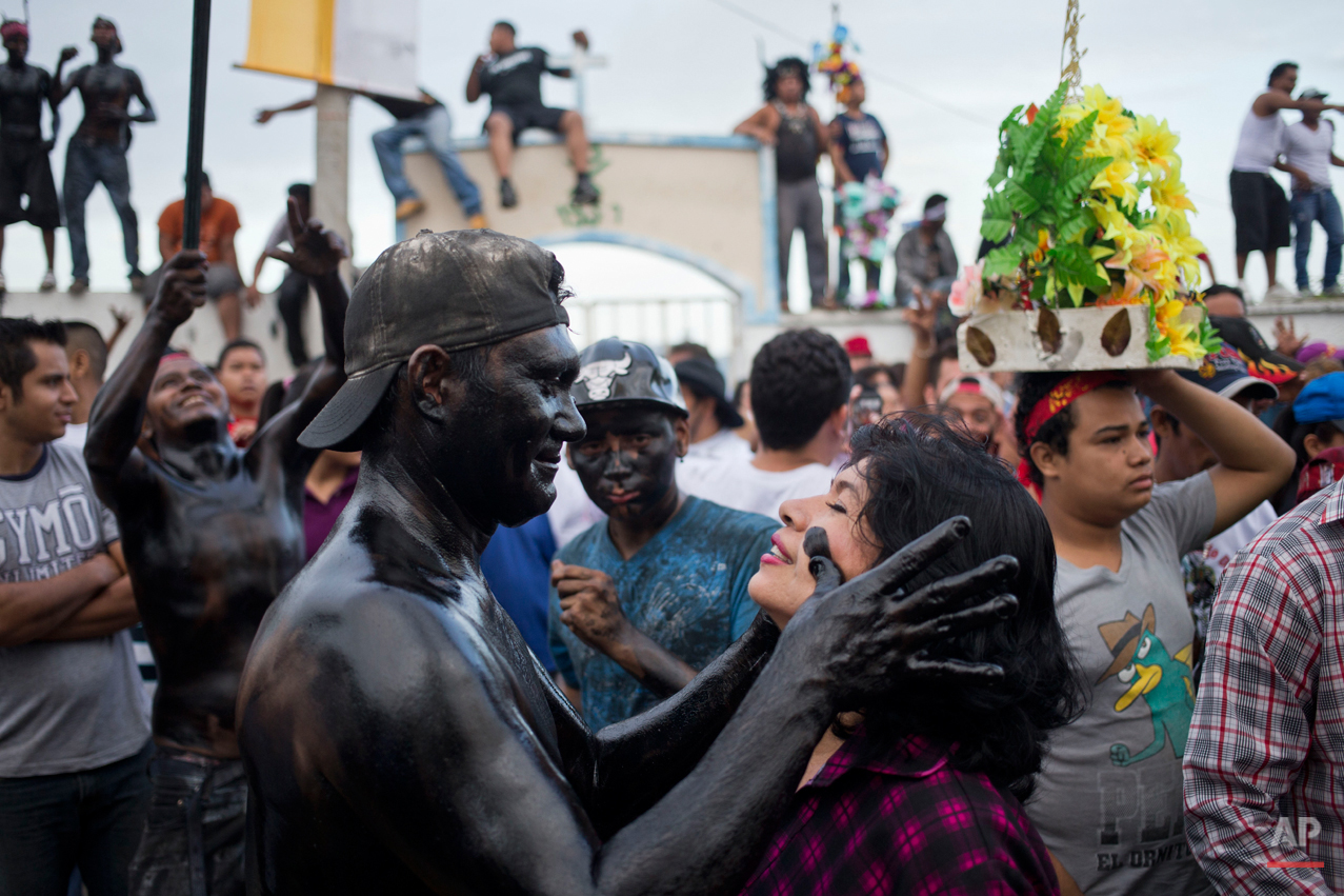 In this July. 31, 2015 photo, a devotee smears a woman's face with black recycled motor oil, during the celebration of the feast of Managua's patron saint, Santo Domingo de Guzman, in Managua, Nicaragua. Covered in motor oil revelers and devotees dance as a way to pay for a perceived miracle performed by the saint. (AP Photo/Esteban Felix)