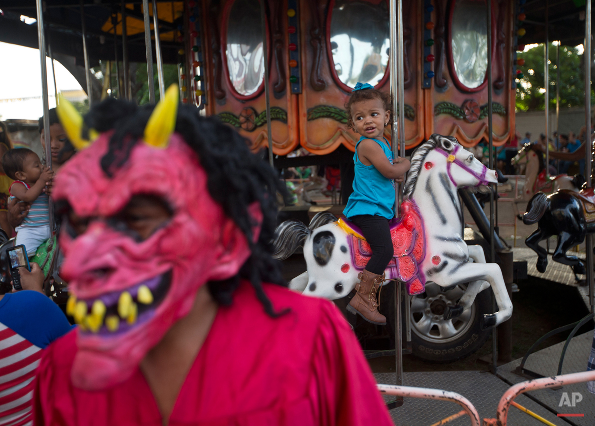In this Aug. 4, 2015 photo, a devotee, wears a devil's mask next to a merry-go-round, during Managua's patron saint, Santo Domingo de Guzman's celebration, in Managua, Nicaragua. The festivities are syncretic in nature, being linked to the corn harvest and the regionís indigenous corn god Xolotl. (AP Photo/Esteban Felix)