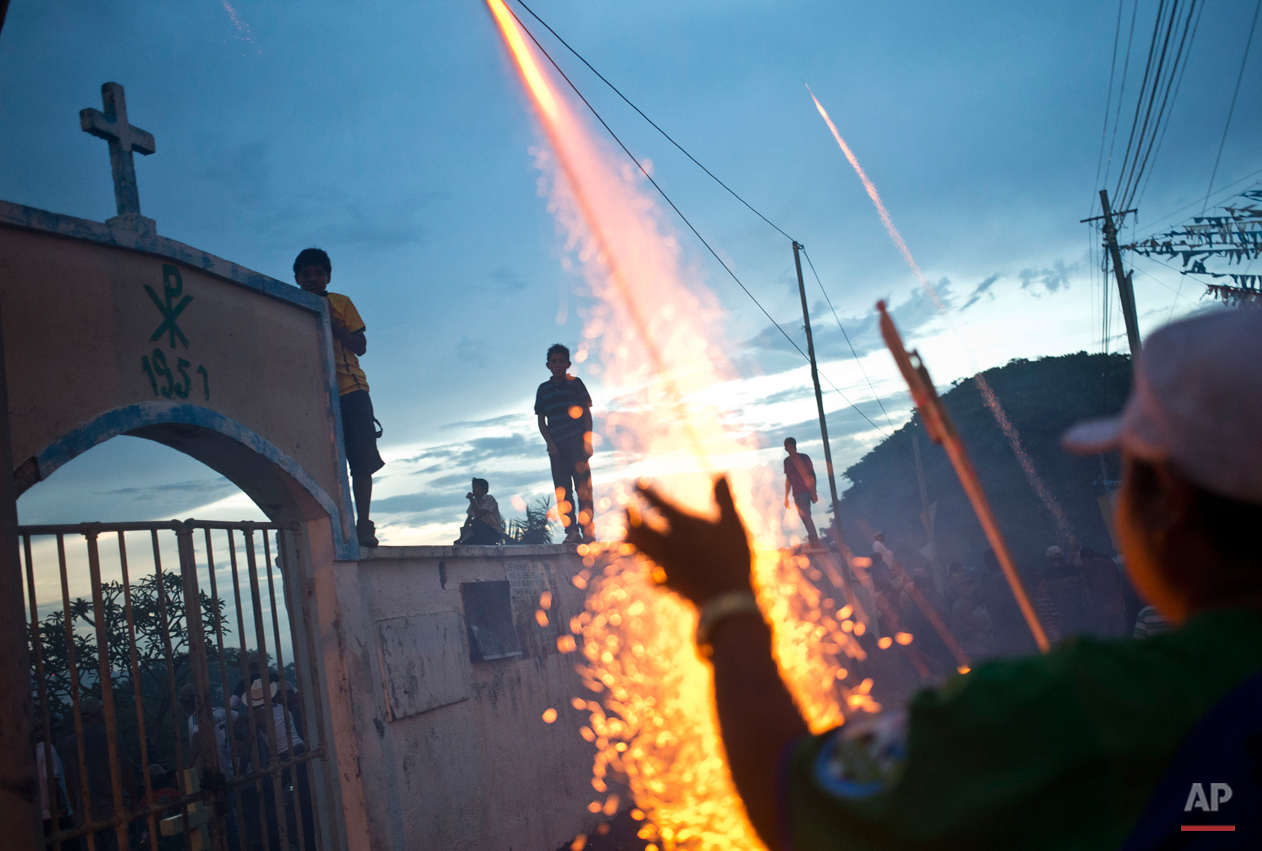 In this Aug. 10, 2015, photo, a fireworks vendor launches a rocket during Managua's patron saint, Santo Domingo de Guzman's celebration, in Managua, Nicaragua. Vendors hawk all kinds of religious items, carnival food, games of chance, toys and popular art, while the devout pay their promise to the saint. (AP Photo/Esteban Felix)
