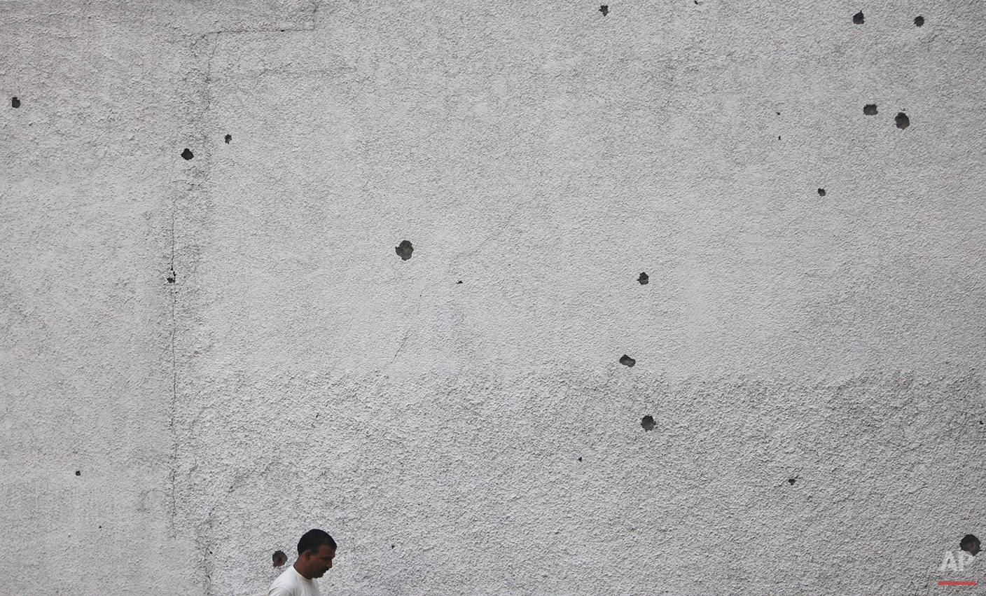 In this Sunday, Aug. 23, 2015, photo, an Indian border villager walks past a wall of a house with marks of mortar shells Ranbir Singh Pura 36 kilometers (23 miles) from Jammu, India. On the face of it these villages in the Jammu region of Indian Kashmir seem idyllic, but over the last two weeks these villages have been witness to an angry exchange of fire and mortar shells between Indian and Pakistani soldiers. This isn't the first time that these villages have borne the brunt of the animosity between India and archrival Pakistan. And this likely won't be the last. (AP Photo/Channi Anand)