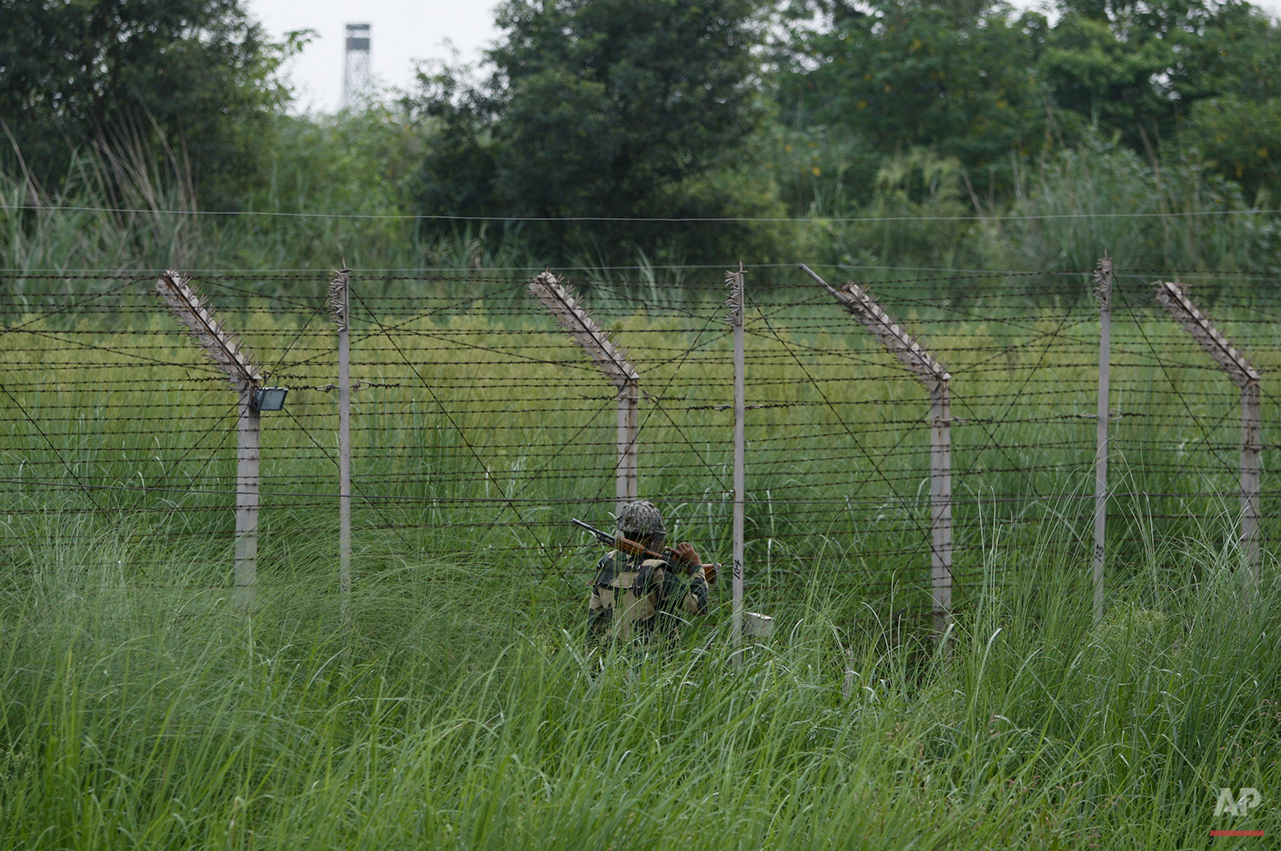 In this Sunday, Aug. 9, 2015, photo, an Indian Border Security Force soldier patrols along the Pargwal area of India-Pakistan international border in Akhnoor,  sector 33 kilometers (21 miles) from Jammu, India. On the face of it these villages in the Jammu region of Indian Kashmir seem idyllic, but over the last two weeks these villages have been witness to an angry exchange of fire and mortar shells between Indian and Pakistani soldiers. This isn't the first time that these villages have borne the brunt of the animosity between India and archrival Pakistan. And this likely won't be the last. (AP Photo/Channi Anand)
