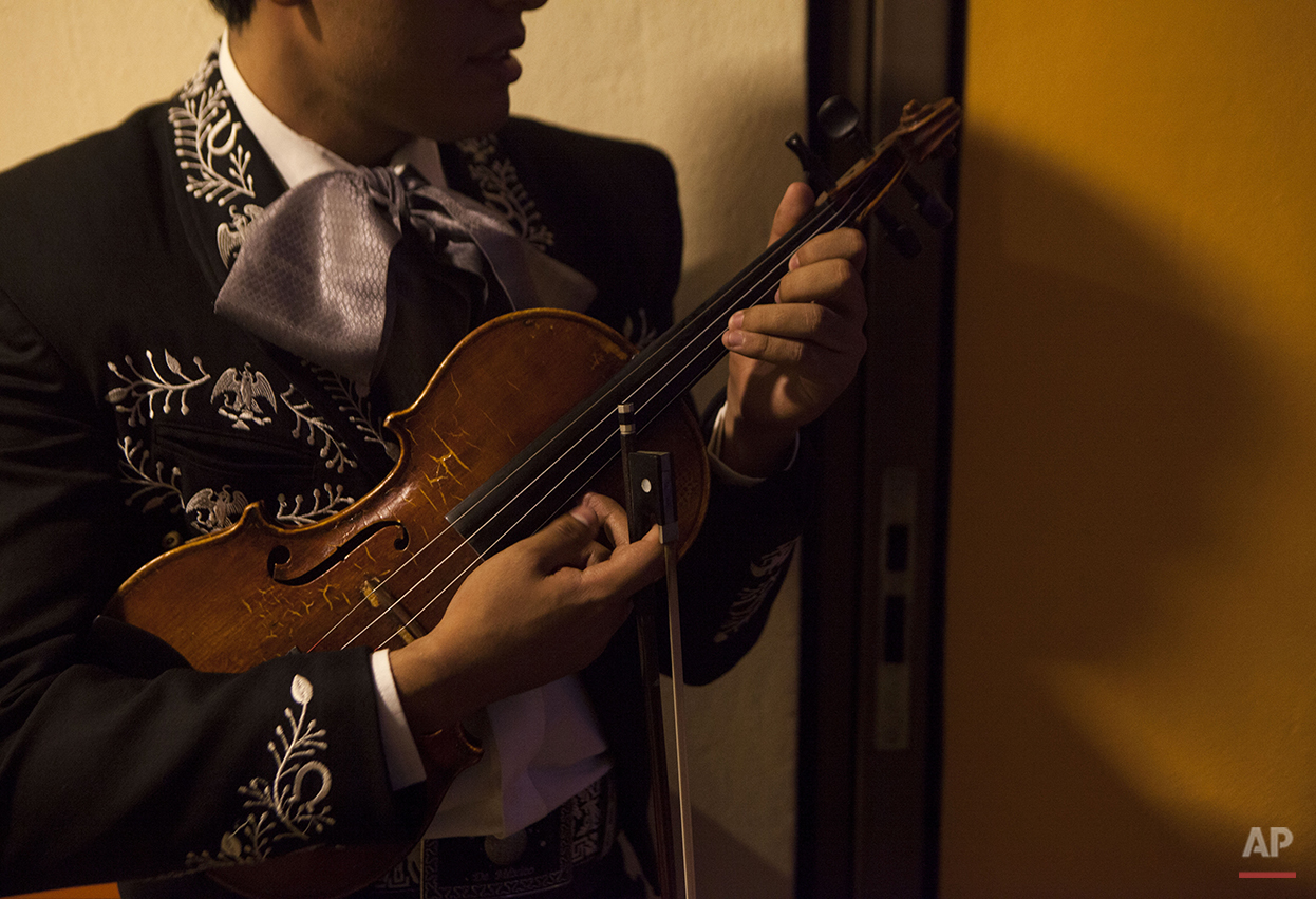 In this Aug. 21, 2015 photo, mariachi Carlos Castaneda plucks his violin as he waits for customers at the Tenampa Salon restaurant and bar in Garibaldi Plaza in Mexico City. Traditional mariachi groups usually have at least two violinists, and Castaneda plays alongside his brother, Oscar. He added that mariachi music is a family tradition. (AP Photo/Sofia Jaramillo)