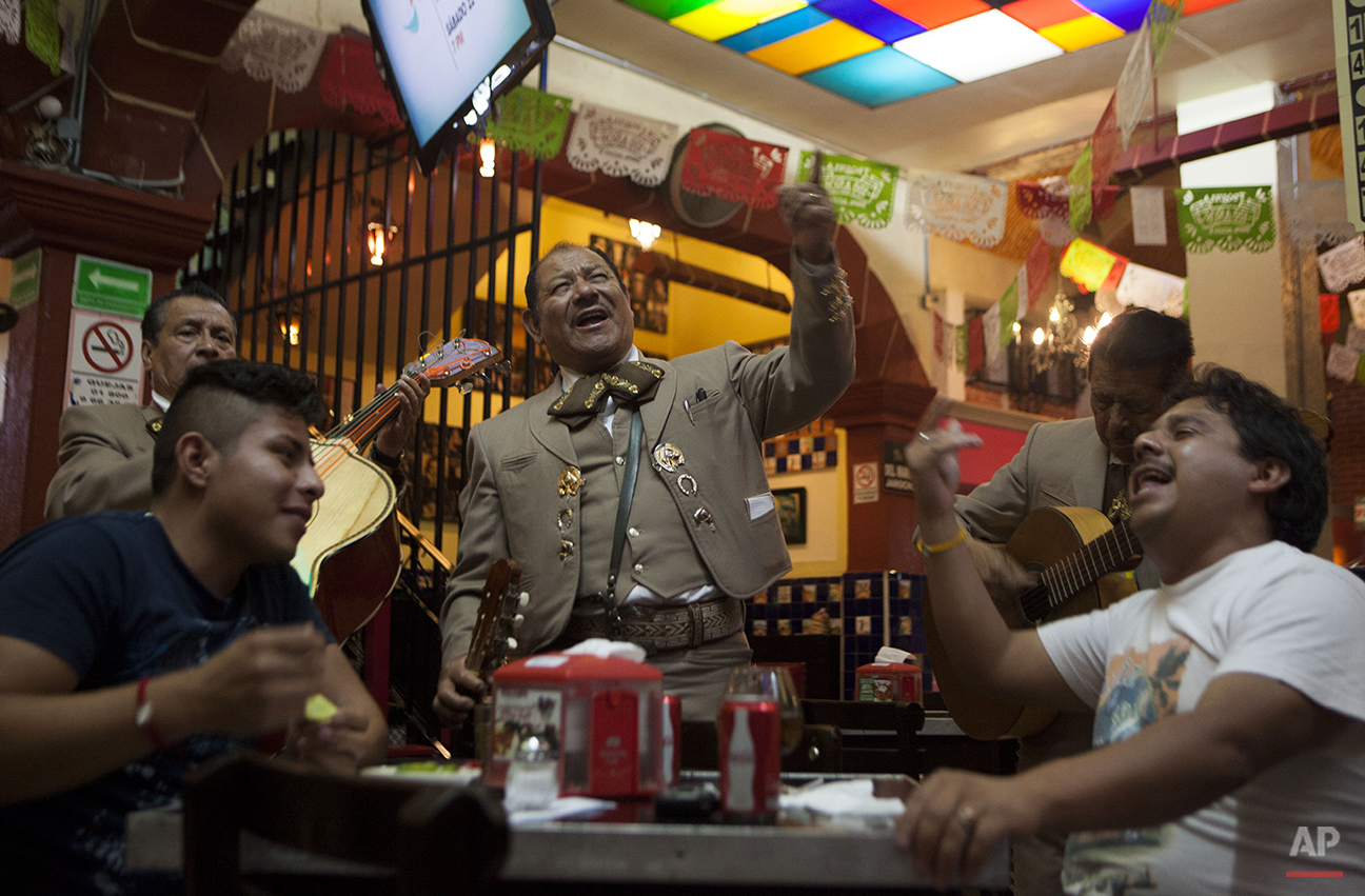 In this Aug. 20, 2015 photo, mariachi Jaime Gamez sings for paying customers Pedro Fuentes, left, and Manuel Cortez inside the Salon Tenampa bar and restaurant in Garibaldi Plaza in Mexico City.  The restaurant's founder brought the traditions of tequila and mariachi to Mexico City from his native Jalisco state and has filled the restaurant with partiers since 1925. (AP Photo/Sofia Jaramillo)