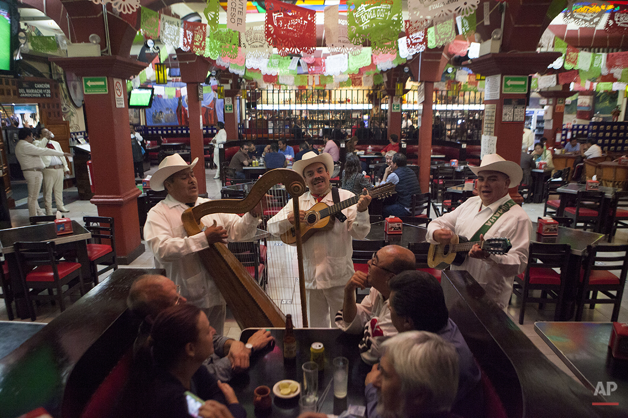 In this Aug. 12, 2015 photo, a jarocho band plays for patrons inside Salon Tenampa restaurant and bar in Garibaldi Plaza in Mexico City. The local is famous for its tradition of mariachi music, but also jarocho music from the Gulf state of Veracruz, with players standing apart in their white guayabera shirts, pants, and hats. The genre uses a harp and jarana, a small guitar-shaped instrument with eight strings. (AP Photo/Sofia Jaramillo)