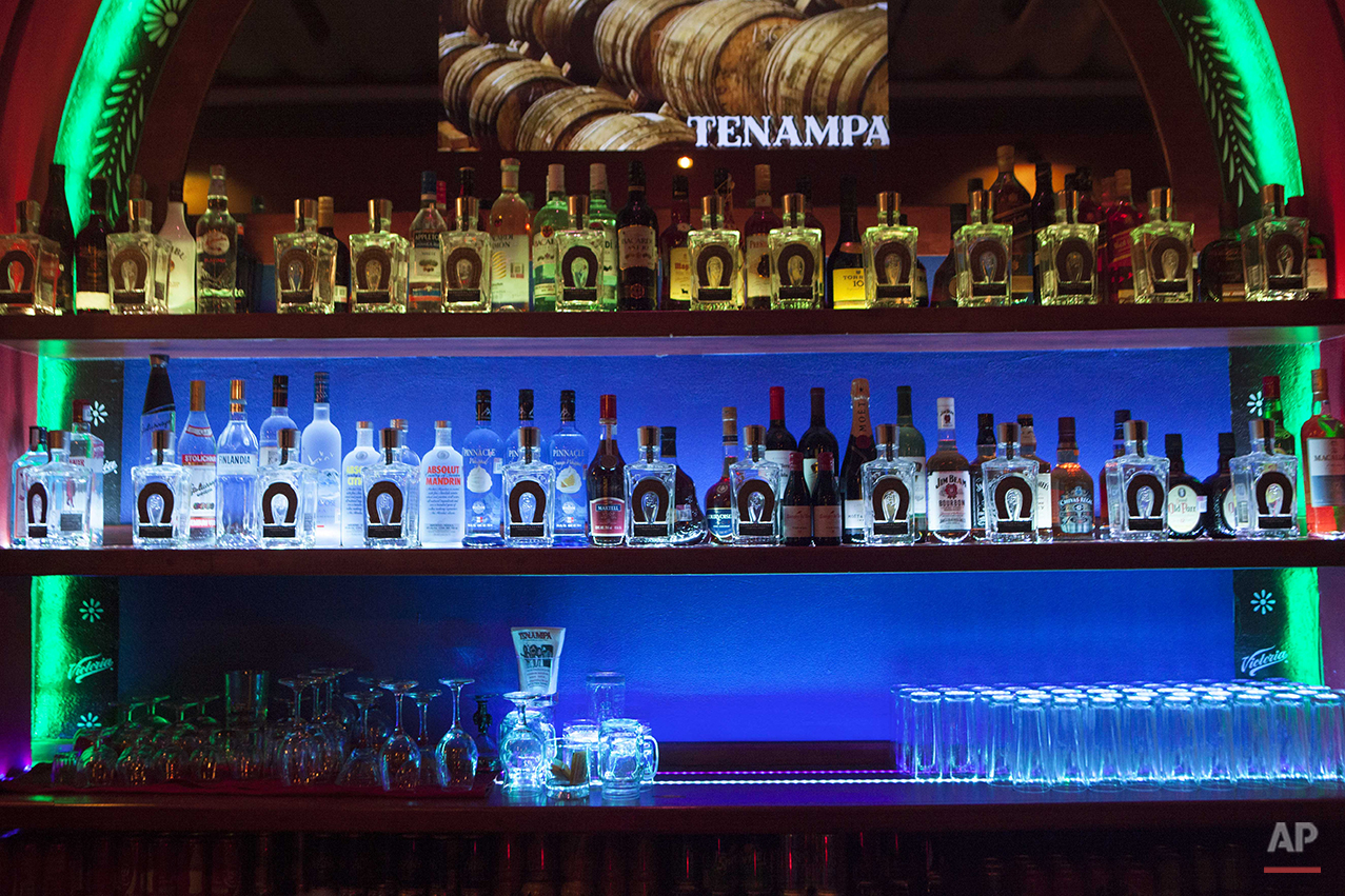 In this Aug. 21, 2015 photo, tequila fills the upstairs bar at the Tenampa Salon restaurant in Mexico City. The original bar was constructed in 1925 when the restaurant was founded, and this year to celebrate its 90th anniversary, a terrace was opened with a view of Garibaldi Plaza. (AP Photo/Sofia Jaramillo)