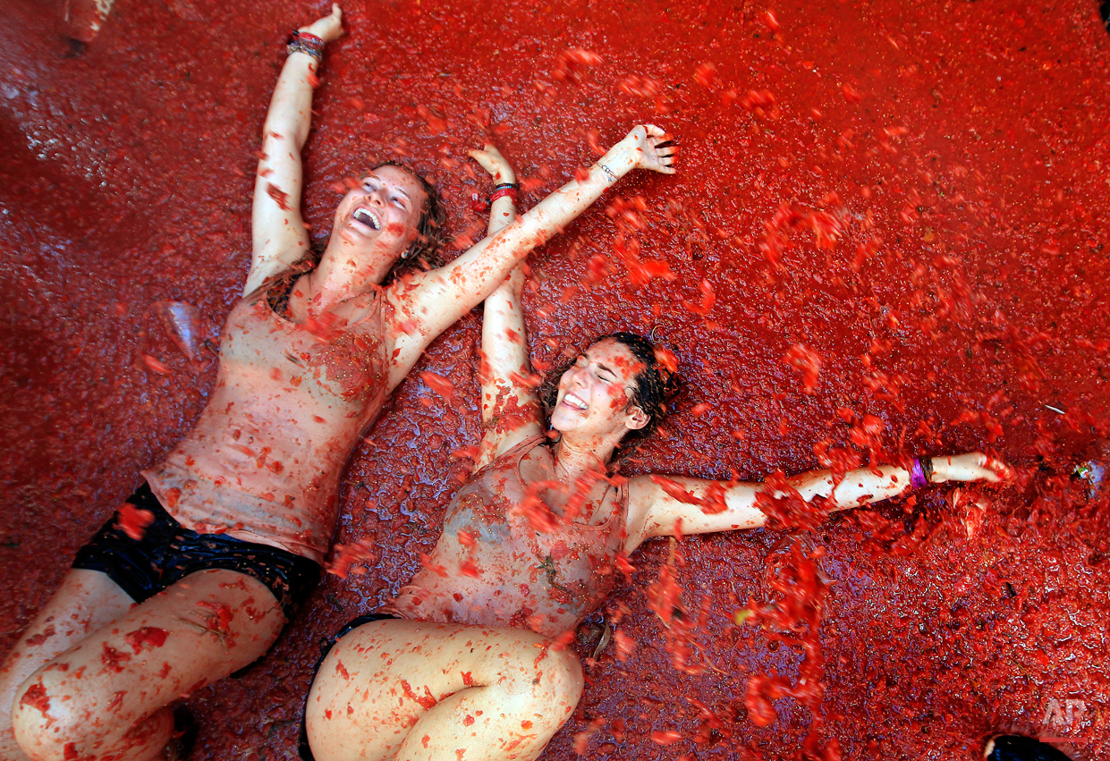 """Two woman lie in a puddle of squashed tomatoes during the annual """"tomatina"""" tomato fight fiesta, in the village of Bunol, 50 kilometers outside Valencia, Spain, Wednesday, Aug. 26, 2015. The streets of an eastern Spanish town are awash with red pulp as thousands of people pelt each other with tomatoes in the annual """"Tomatina"""" battle that has become a major tourist attraction. At the annual fiesta in Bunol on Wednesday, trucks dumped 150 tons of ripe tomatoes for some 22,000 participants, many from abroad to throw during the hour-long morning festivities. (AP Photo/Alberto Saiz)"""