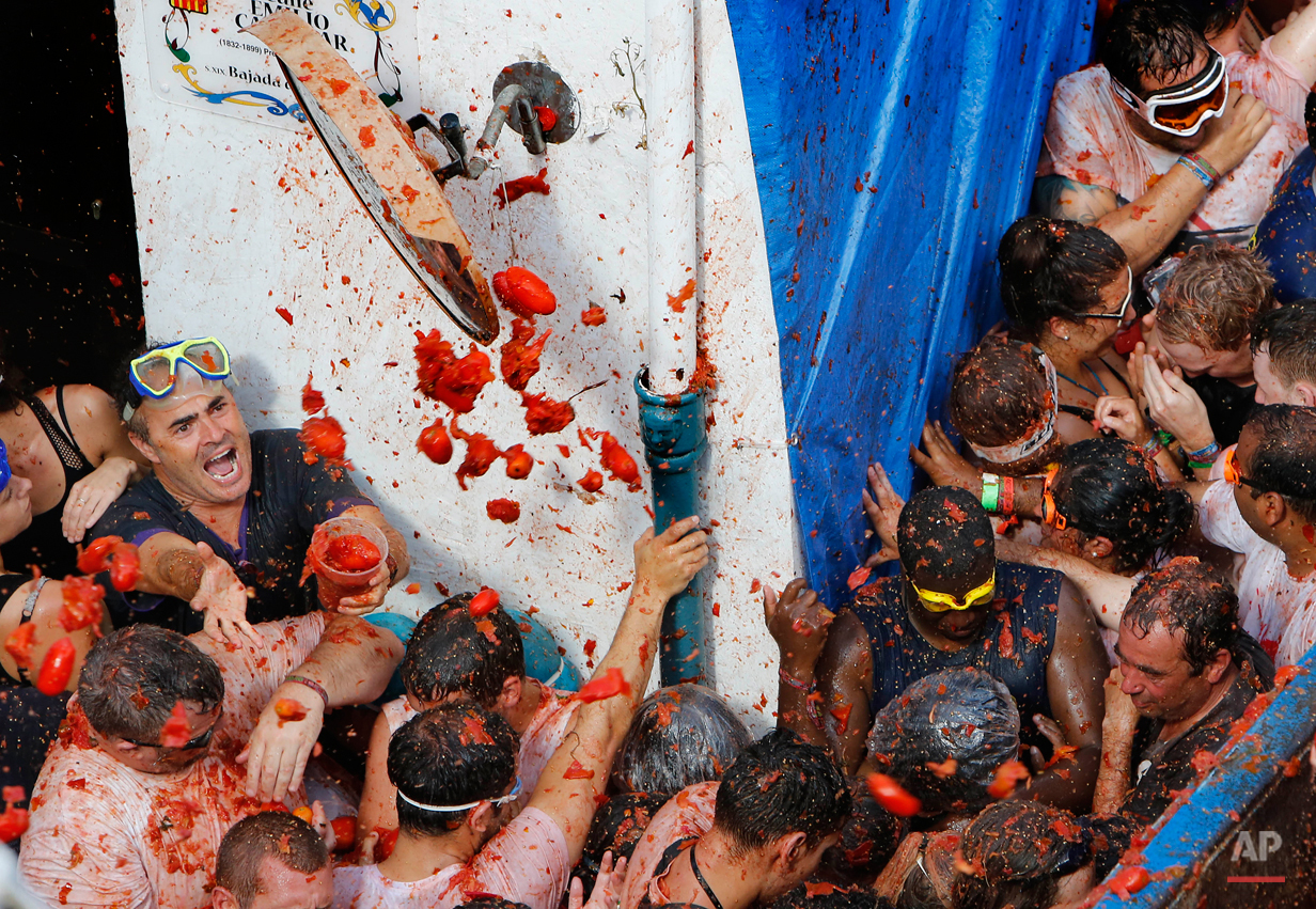 """Crowds of people throw tomatoes at each other, during the annual """"tomatina"""" tomato fiesta, in the village of Bunol, 50 kilometers from Valencia, Spain, Wednesday, Aug. 26, 2015. The streets of an eastern Spanish town are awash with red pulp as thousands of people pelt each other with tomatoes in the annual """"Tomatina"""" battle that has become a major tourist attraction. At the annual fiesta in Bunol on Wednesday, trucks dumped 150 tons of ripe tomatoes for some 22,000 participants, many from abroad to throw during the hour-long morning festivities. (AP Photo/Alberto Saiz)"""