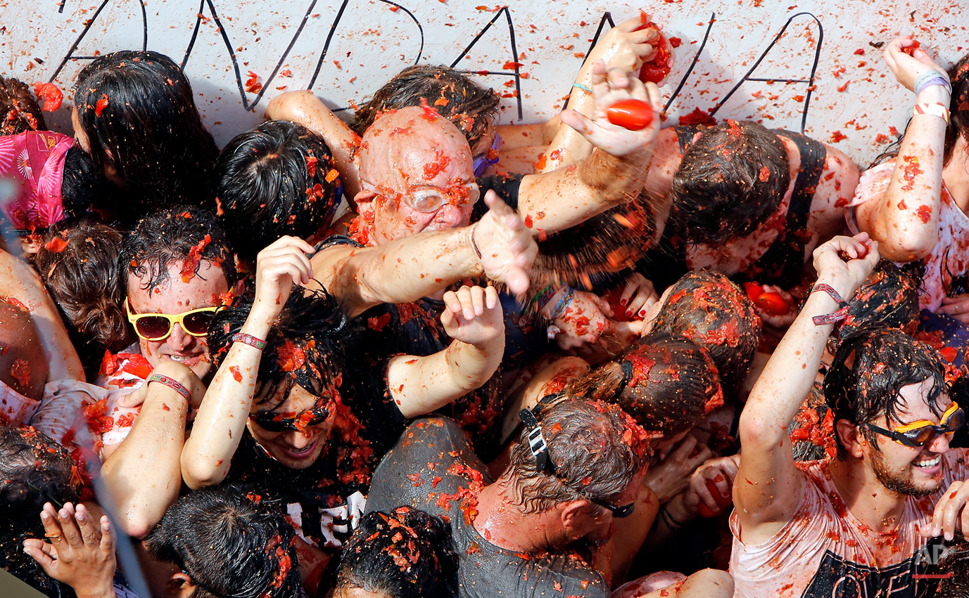 """Crowds of people throw tomatoes at each other during the annual """"tomatina"""" tomato fiesta, in the village of Bunol, 50 kilometers outside Valencia, Spain, Wednesday, Aug. 26, 2015. The streets of an eastern Spanish town are awash with red pulp as thousands of people pelt each other with tomatoes in the annual """"Tomatina"""" battle that has become a major tourist attraction. At the annual fiesta in Bunol on Wednesday, trucks dumped 150 tons of ripe tomatoes for some 22,000 participants, many from abroad to throw during the hour-long morning festivities. (AP Photo/Alberto Saiz)"""
