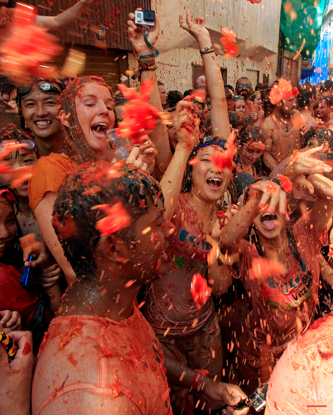 """Crowds of people throw tomatoes at each other, during the annual """"tomatina"""" tomato fight fiesta, in the village of Bunol, 50 kilometers outside Valencia, Spain, Wednesday, Aug. 26, 2015. The streets of an eastern Spanish town are awash with red pulp as thousands of people pelt each other with tomatoes in the annual """"Tomatina"""" battle that has become a major tourist attraction. At the annual fiesta in Bunol on Wednesday trucks dumped 150 tons of ripe tomatoes for some 22,000 participants, many from abroad to throw during the hour-long morning festivities. (AP Photo/Alberto Saiz)"""