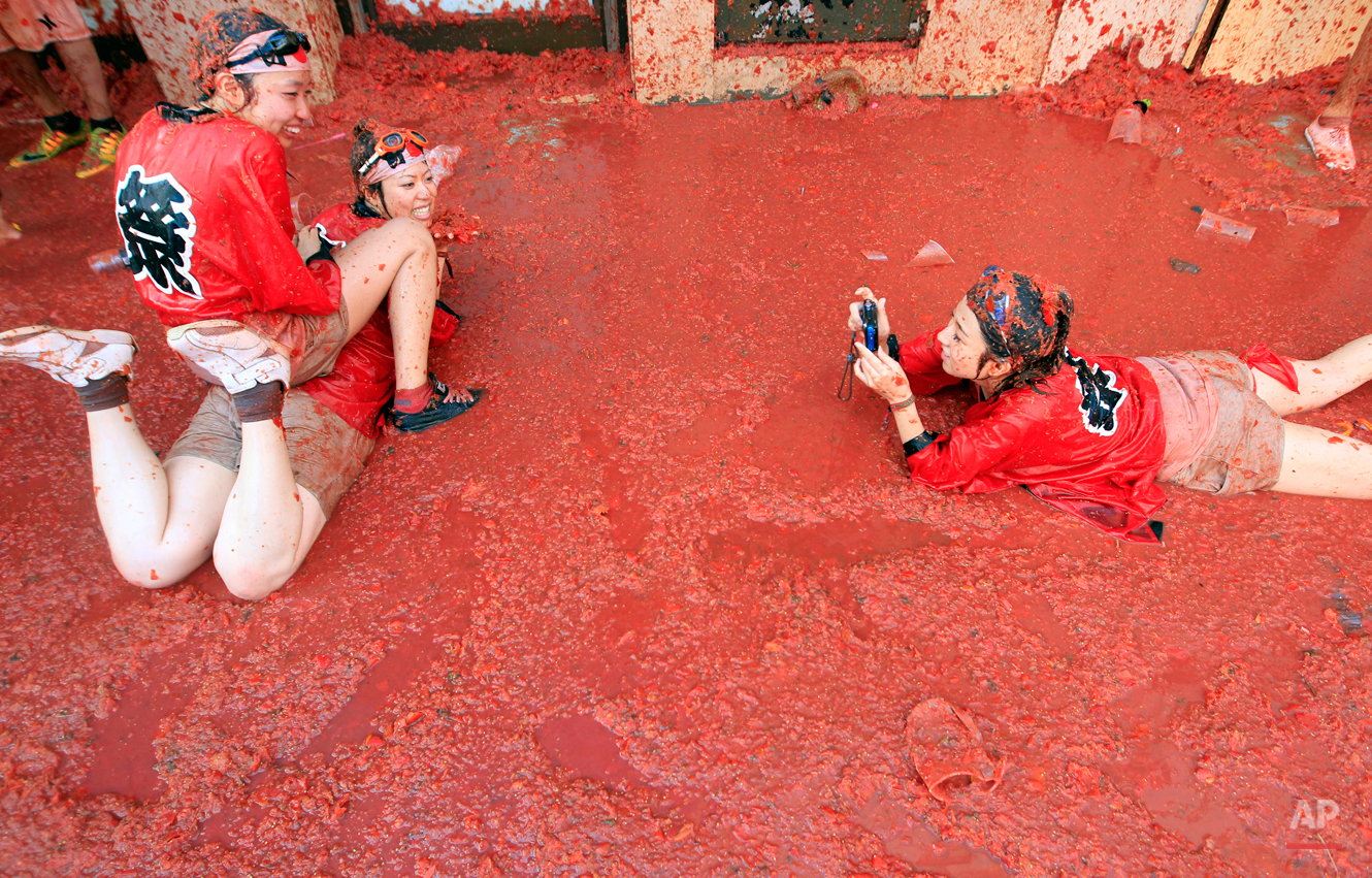 """Two woman have their  photo  taken as they pose in a puddle of squashed tomatoes during the annual """"tomatina"""" tomato fight fiesta, in the village of Bunol, 50 kilometers outside Valencia, Spain, Wednesday, Aug. 26, 2015. The streets of an eastern Spanish town are awash with red pulp as thousands of people pelt each other with tomatoes in the annual """"Tomatina"""" battle that has become a major tourist attraction. At the annual fiesta in Bunol on Wednesday, trucks dumped 150 tons of ripe tomatoes for some 22,000 participants, many from abroad to throw during the hour-long morning festivities. (AP Photo/Alberto Saiz)"""