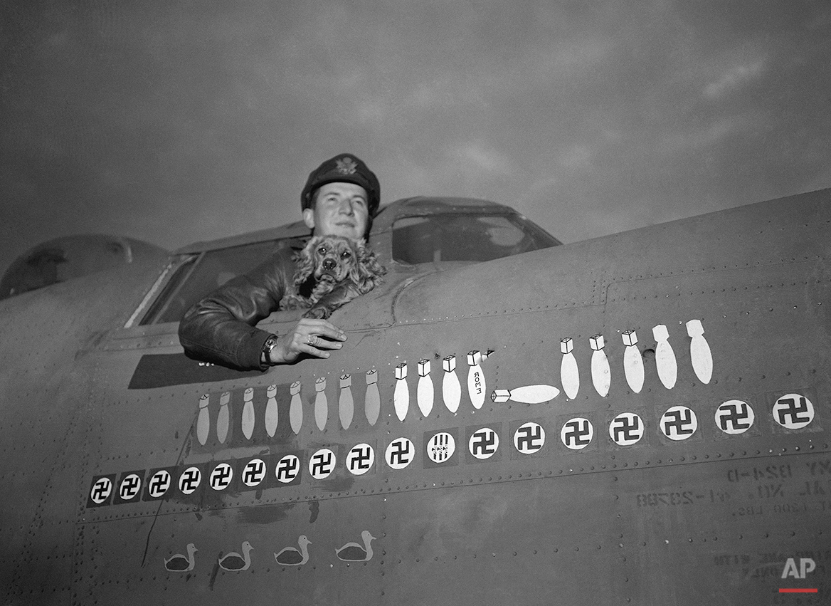 Pilot officer Rusty, mascot of a Liberator operating from this country, was flown to England from the U.S., where he has taken part in numerous bombing raids. Rusty with his owner, First Lieutenant Robert C. Peterson, Navigator of the Liberator on Oct. 25, 1943. (AP Photo)