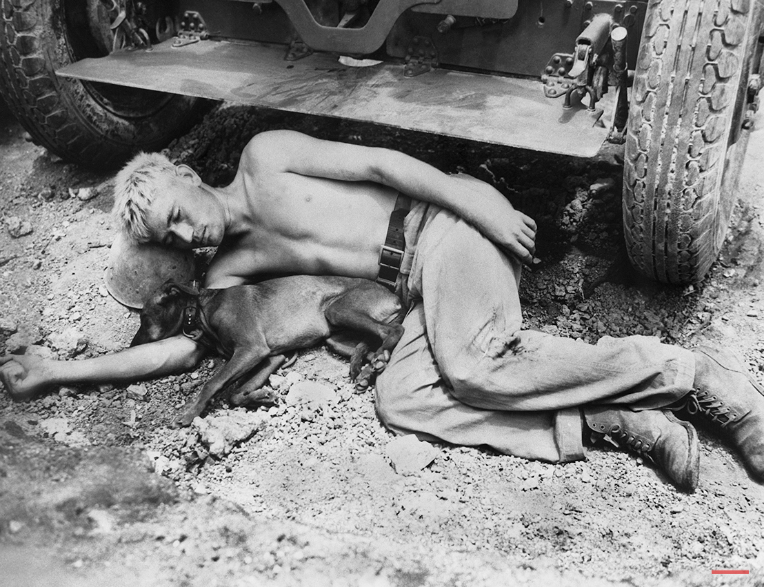 """With his helmet liner as a pillow and the coral ground as his bed, Private John W. Emmons, of 110-20th Avenue, Sheffield, Ala., and his """"friend"""" take a well earned rest in front of a 105mm Howitzer on Okinawa on June 27, 1945. The tired artillery man is with the sixth marine division and his friend is a unit mascot. (AP Photo)"""