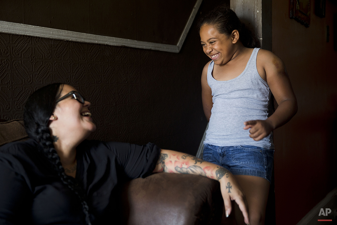 In this July 16, 2015 photo, Marisol Jimenez speaks with her mother Carmen Sharpe at their home in Philadelphia. Marisol's mother decided to get Marisol involved in Work to Ride, a non-profit program at the Chamounix Equestrian Center in Philadelphia's Fairmount Park that helps at-risk children become equestrians while teaching them responsibility and respect. (AP Photo/Matt Rourke)