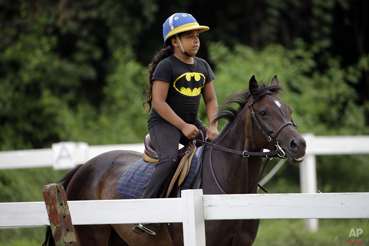 In this July 29, 2015, photo, Work to Ride participant Marisol Jimenez, 9, rides the pony Lyric in Philadelphia. Marisol's mother decided to get Marisol involved in Work to Ride, a non-profit program at the Chamounix Equestrian Center in Philadelphia's Fairmount Park.  (AP Photo/Matt Rourke)