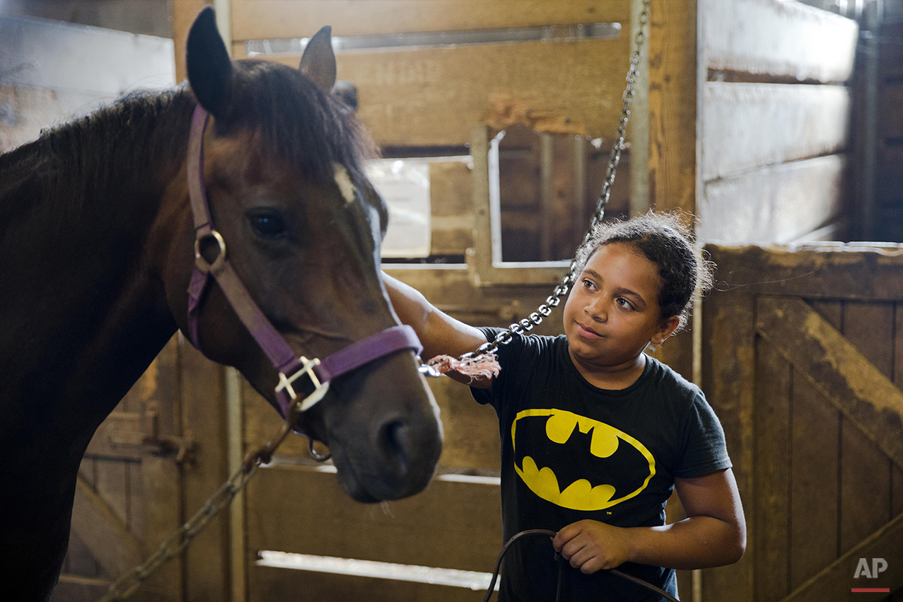 In this July 29, 2015 photo, Work to Ride participant Marisol Jimenez, 9, takes the pony Lyric from its stall in Philadelphia. Marisol and 19 other kids in Work to Ride muck down stalls, brush horses, shovel out hay and droppings, and keep the stables clean and running. In exchange, they receive horseback riding lessons, and a chance to be on their nationally recognized polo team. (AP Photo/Matt Rourke)