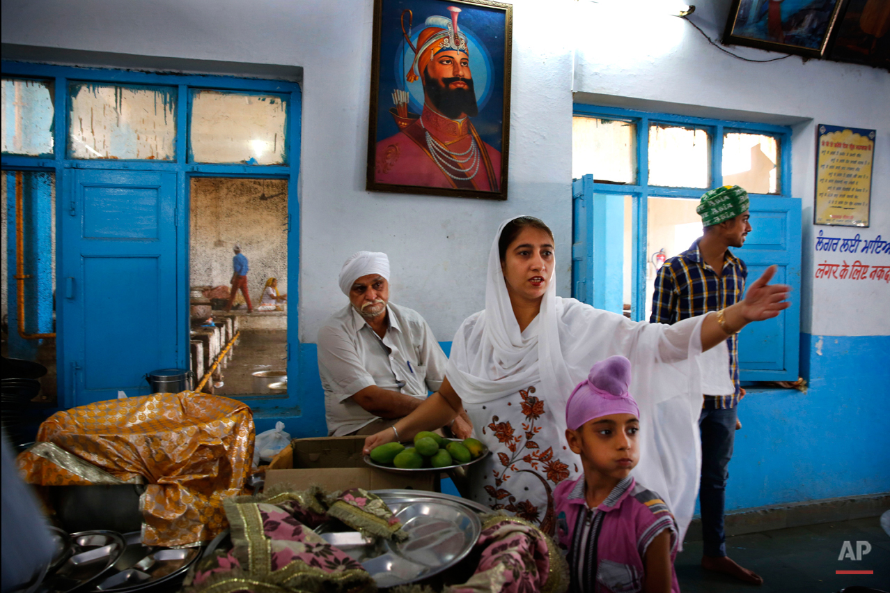 In this June 14, 2015 photo, volunteers and devotees help prepare langar at the Majnu-ka-Tilla Gurudwara or Sikh temple, in New Delhi, India. Langar, or the community meal, was started by Guru Nanak, who founded Sikhism in late 15th century, and is now a tradition followed by more than 30 millions Sikhs worldwide. Nearly every gurudwara in the world, irrespective of size, has a kitchen and serves langar. (AP Photo/Manish Swarup)
