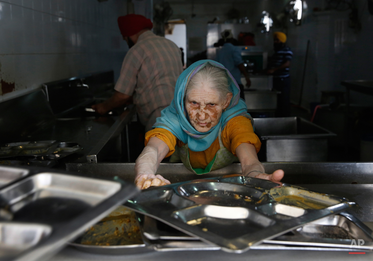 In this May 12, 2015, photo, Paro, uses first name only, collects used plates from devotees for cleaning after they finish langar, which translates to community dinner, at the Bangla Sahib Gurdwara or Sikh temple, in New Delhi, India. Service is one of the most integral traditions of gurudwaras. From cleaning to preparing tons of food every day there is plenty of work to be done. And there are plenty of sevadaars, or volunteers, to do it. While the gurudwara employs a small group of men to help manage the kitchen, it depends on visiting worshippers to contribute nearly half of all work and food supplies. (AP Photo/Manish Swarup)