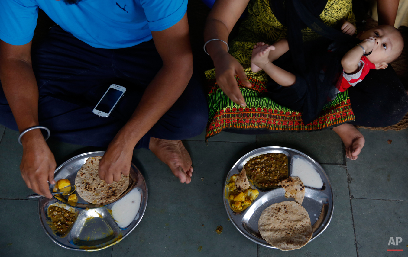 In this June 14, 2015 photo, a family eats langar at the Majnu-ka-Tilla Gurudwara or Sikh temple, in New Delhi, India. Langar, which translates to community dinner, was started by Guru Nanak, who founded Sikhism in late 15th century, and is now a tradition followed by more than 30 millions Sikhs worldwide. Nearly every gurudwara in the world, irrespective of size, has a kitchen and serves langar. (AP Photo/Manish Swarup)