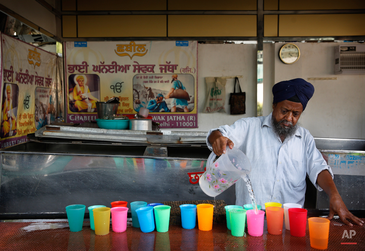 In this June 3, 2015, photo,  a Sikh devotee pours drinking water in glasses to be served during langar outside a hall at the Bangla Sahib Gurudwara or Sikh temple, in New Delhi, India. Service is one of the most integral traditions of gurudwaras. From cleaning to preparing tons of food every day there is plenty of work to be done. And there are plenty of sevadaars, or volunteers, to do it. While the gurudwara employs a small group of men to help manage the kitchen, it depends on visiting worshippers to contribute nearly half of all work and food supplies. (AP Photo/Manish Swarup)