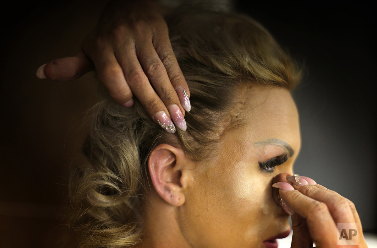 In this Sunday, Sept. 18, 2016 photo, Britanie Eichenholc, from France, applies make up ahead of the Miss Trans Star International 2016 show celebrated in Barcelona, Spain. (AP Photo/Emilio Morenatti)