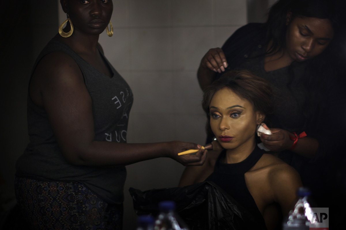 In this Sunday, Sept. 18, 2016 photo, Sahhara, from Nigeria, is made up by friends ahead of the Miss Trans Star International 2016 celebrated in Barcelona, Spain. To be eligible to compete, contestants are not required to have undergone gender reassignment surgery, but must have the face and figure that comports with traditional notions of what constitutes ideal feminine beauty. (AP Photo/Emilio Morenatti)