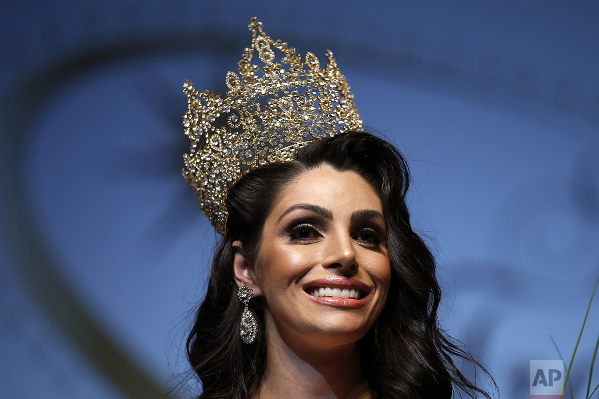 In this Sunday, Sept. 18, 2016 photo, the representative of Brazil, Rafaela Manfrini, smiles wearing the crown of the new Miss International Trans Star 2016, during a show celebrated in Barcelona, Spain. To be eligible to compete, contestants are not required to have undergone gender reassignment surgery, but must have the face and figure that comports with traditional notions of what constitutes ideal feminine beauty. (AP Photo/Manu Fernandez)