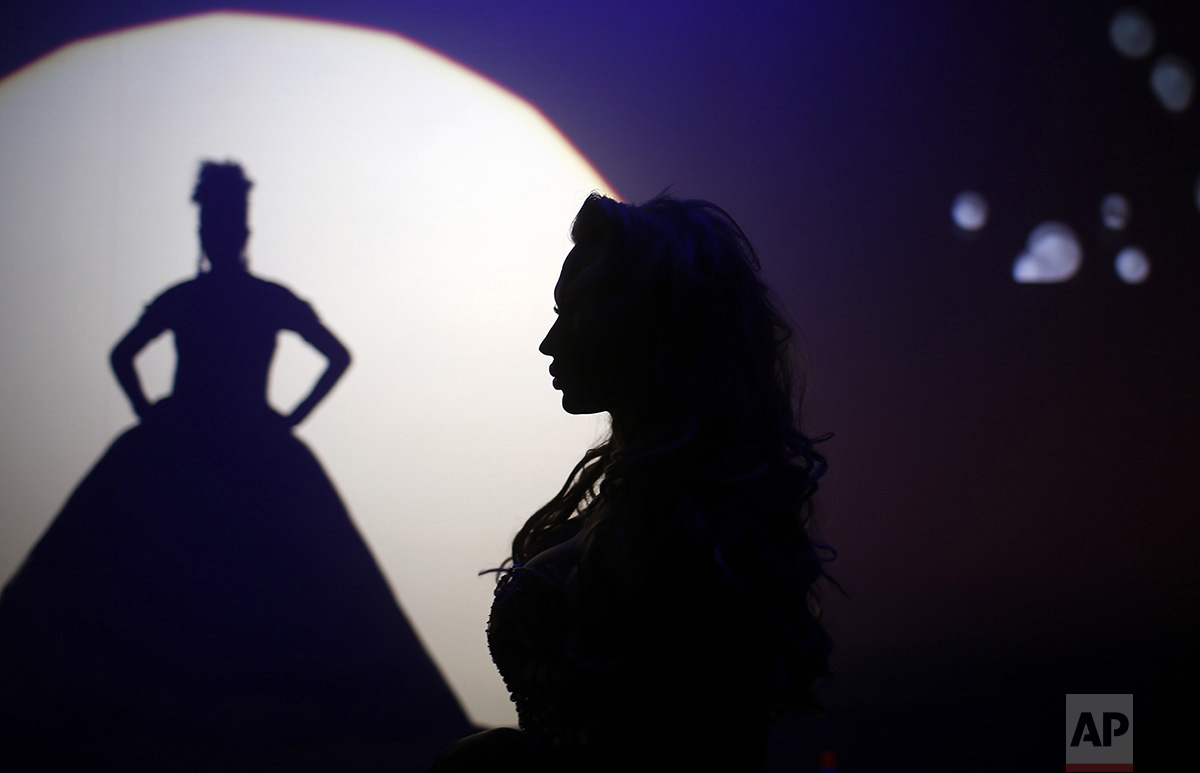In this Sunday, Sept. 18, 2016 photo, Britanie Eichenholc, from France, right, is seen silhouetted during her performance at the Miss Trans Star International 2016 show celebrated in Barcelona, Spain. (AP Photo/Manu Fernandez)
