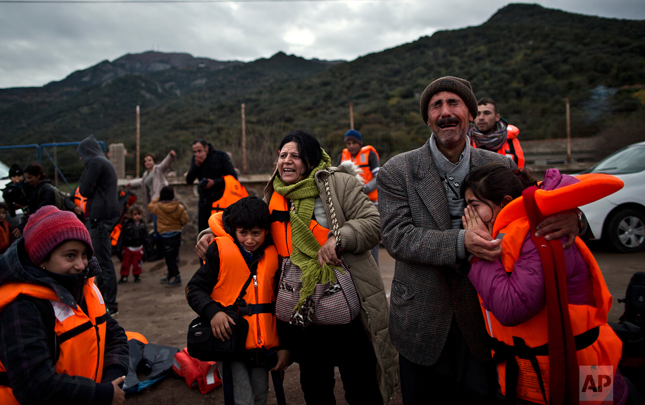 In this Thursday, Dec. 3, 2015 photo, Yazidi refugee Samir Qasu, 45, right, from Sinjar, Iraq, and his wife Bessi, 42, cry while embracing their children, Dunia, 13, and Dildar, 10, shortly after arriving on a vessel from the Turkish coast to the northeastern Greek island of Lesbos. (AP Photo/Muhammed Muheisen)