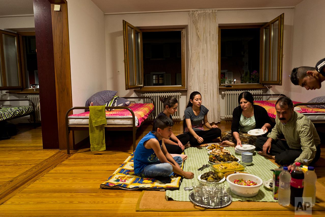 In this Tuesday, Sept. 13, 2016 photo, Yazidi migrant family, from Sinjar, Iraq, from right to left, Dilshad Qasu, 18, Samir Qasu, 46, Bessi Qasim, 43, Delphine Qasu, 19, Dunia Qasu, 14, and Dildar Qasu, 11, sit on the ground while having their dinner at their apartment in Elzach, Germany.(AP Photo/Muhammed Muheisen)