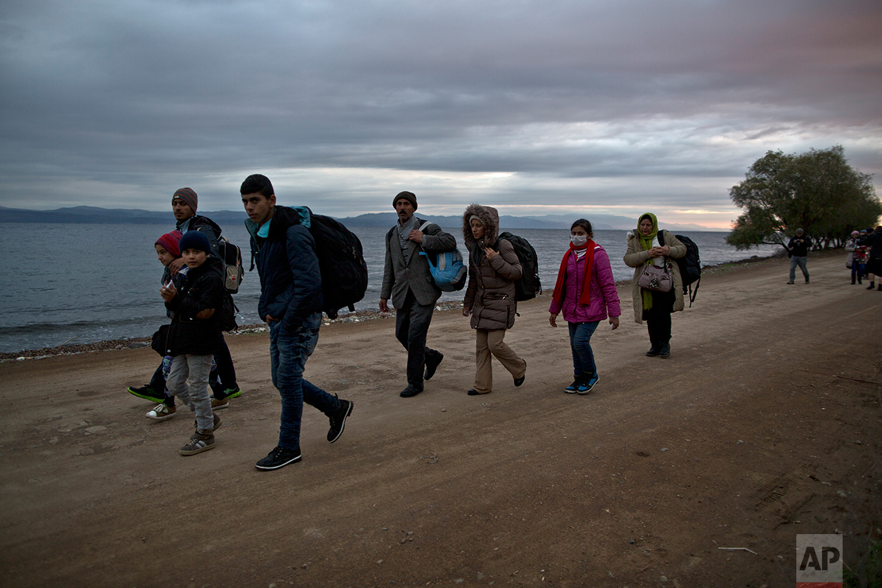 In this Thursday, Dec. 3, 2015 photo, Yazidi refugee Samir Qasu, 45, from Sinjar, Iraq, and his wife Bessi, 42, their two daughters Delphine, 18, Dunia 13, and their two sons Dilshad, 17, and Dildar, 10, walk toward a gathering point to board a bus to a registration center, after arriving on a vessel from the Turkish coast to the northeastern Greek island of Lesbos. (AP Photo/Muhammed Muheisen)