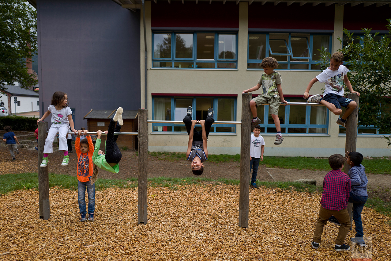 In this Thursday, Sept. 15, 2016 photo, Dildar Qasu, 11, center, a Yazidi migrant from Sinjar, Iraq, plays at his school's play ground during a break at Schulzentrum Oberes Elztal, in Elzach, Germany. (AP Photo/Muhammed Muheisen)