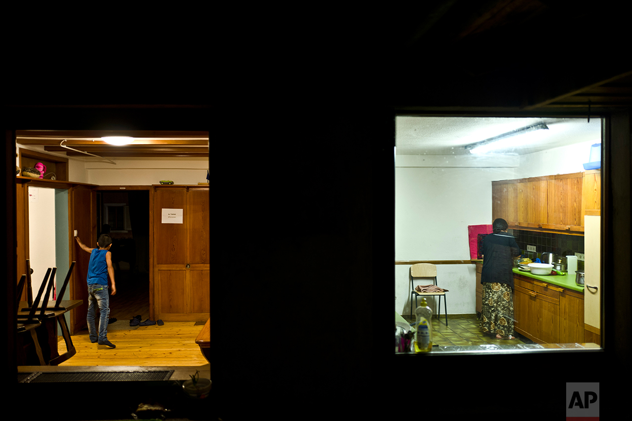 In this Tuesday, Sept. 13, 2016 photo, Bessi Qasim, 43, right, a Yazidi migrant from Sinjar, Iraq, cooks in her kitchen, while her son Dildar Qasu, 11, left, talks with their neighbor at their apartment in Elzach, Germany. (AP Photo/Muhammed Muheisen)
