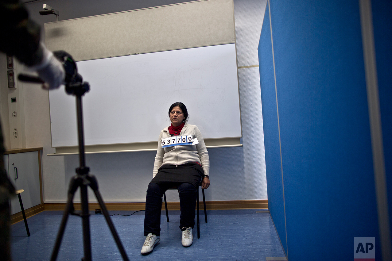In this Wednesday, Dec. 9, 2015 photo, a German army officer takes a head shot of Bessi Qasim, 42, a Yazidi refugee from Sinjar, Iraq, as part of her asylum seeking process, at the Central Registration Centre in Patrick Henry Village in Heidelberg, Germany. (AP Photo/Muhammed Muheisen)