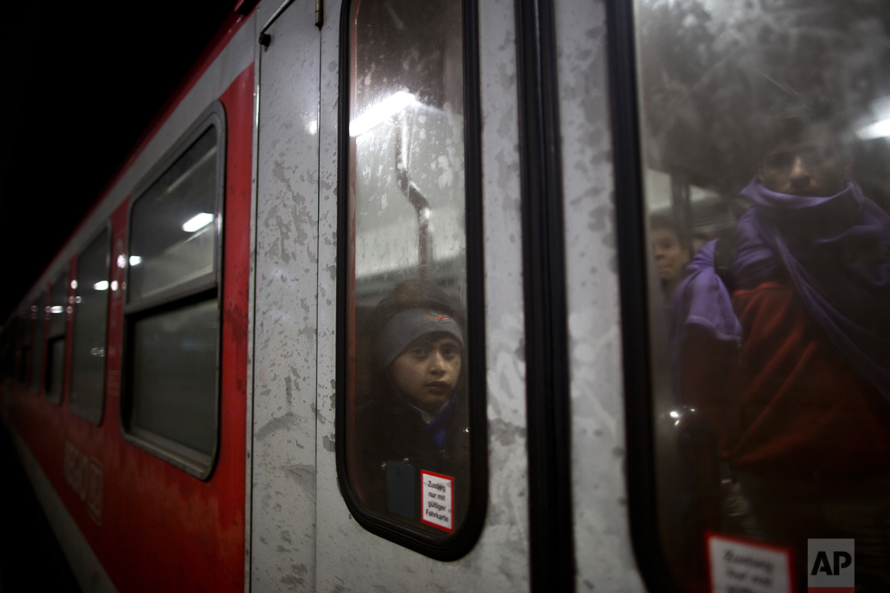 In this Tuesday, Dec. 8, 2015 photo, Dildar Qasu, 10, a Yazidi refugee from Sinjar, Iraq, leans on the door of the train as it arrives to  Mannheim, Germany, coming from Freilassing. (AP Photo/Muhammed Muheisen)