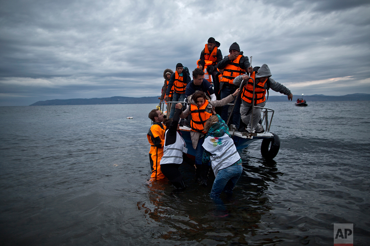In this Thursday, Dec. 3, 2015 photo, volunteers help refugees disembark from a vessel carrying Yazidi refugee Samir Qasu, 45, from Sinjar, Iraq, and his wife Bessi, 42, their two daughters Delphine, 18, seen center left, Dunia 13, and their two sons Dilshad, 17, seen center left, and Dildar, 10, as it arrives to the northeastern Greek island of Lesbos from the Turkish coast. (AP Photo/ Muhammed Muheisen)