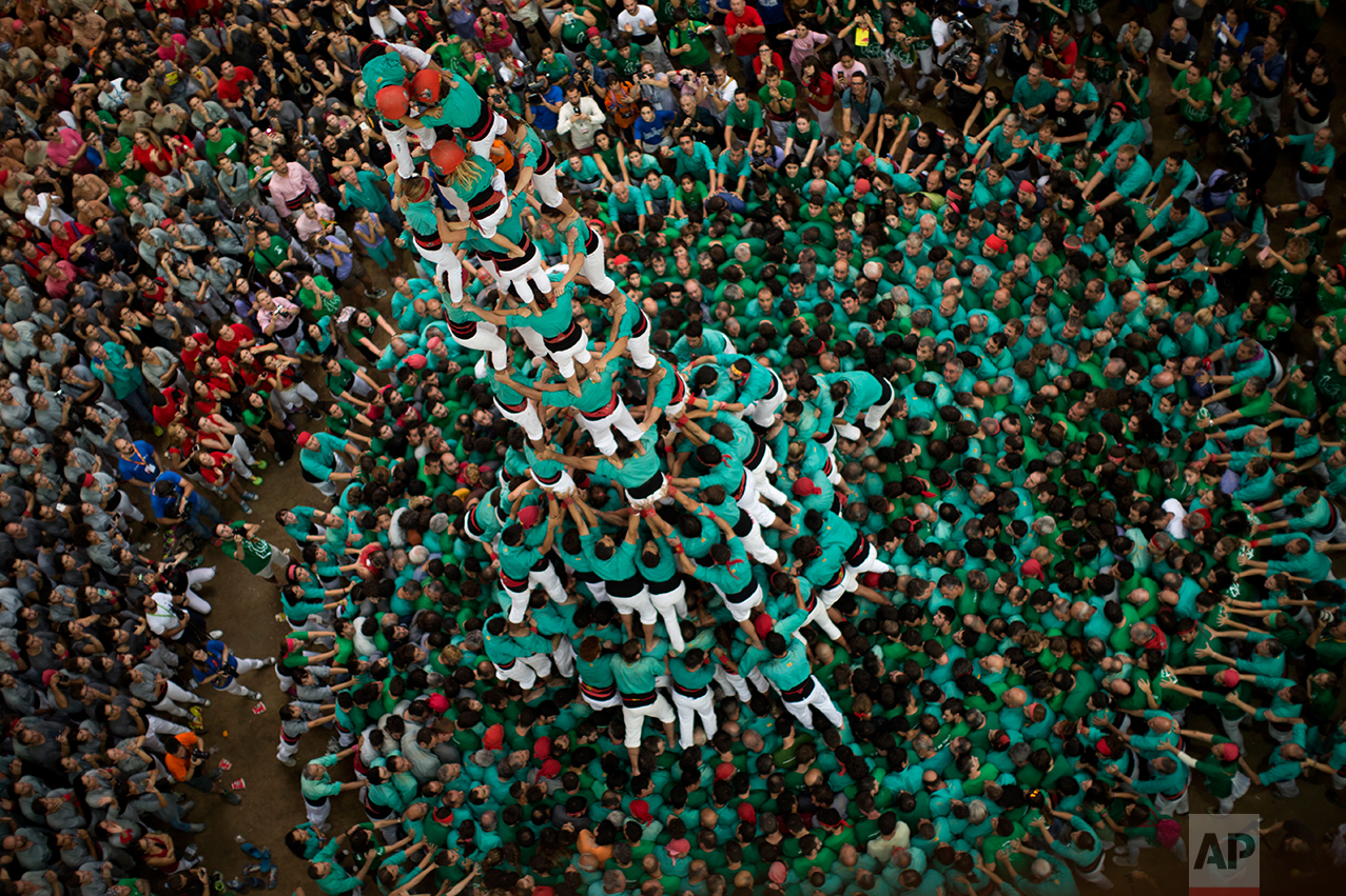 "Members of the ""Castellers de Villafranca"" try to complete their human tower during the 26th Human Tower Competition in Tarragona, Spain, on Sunday, Oct. 2, 2016. (AP Photo/Emilio Morenatti)"