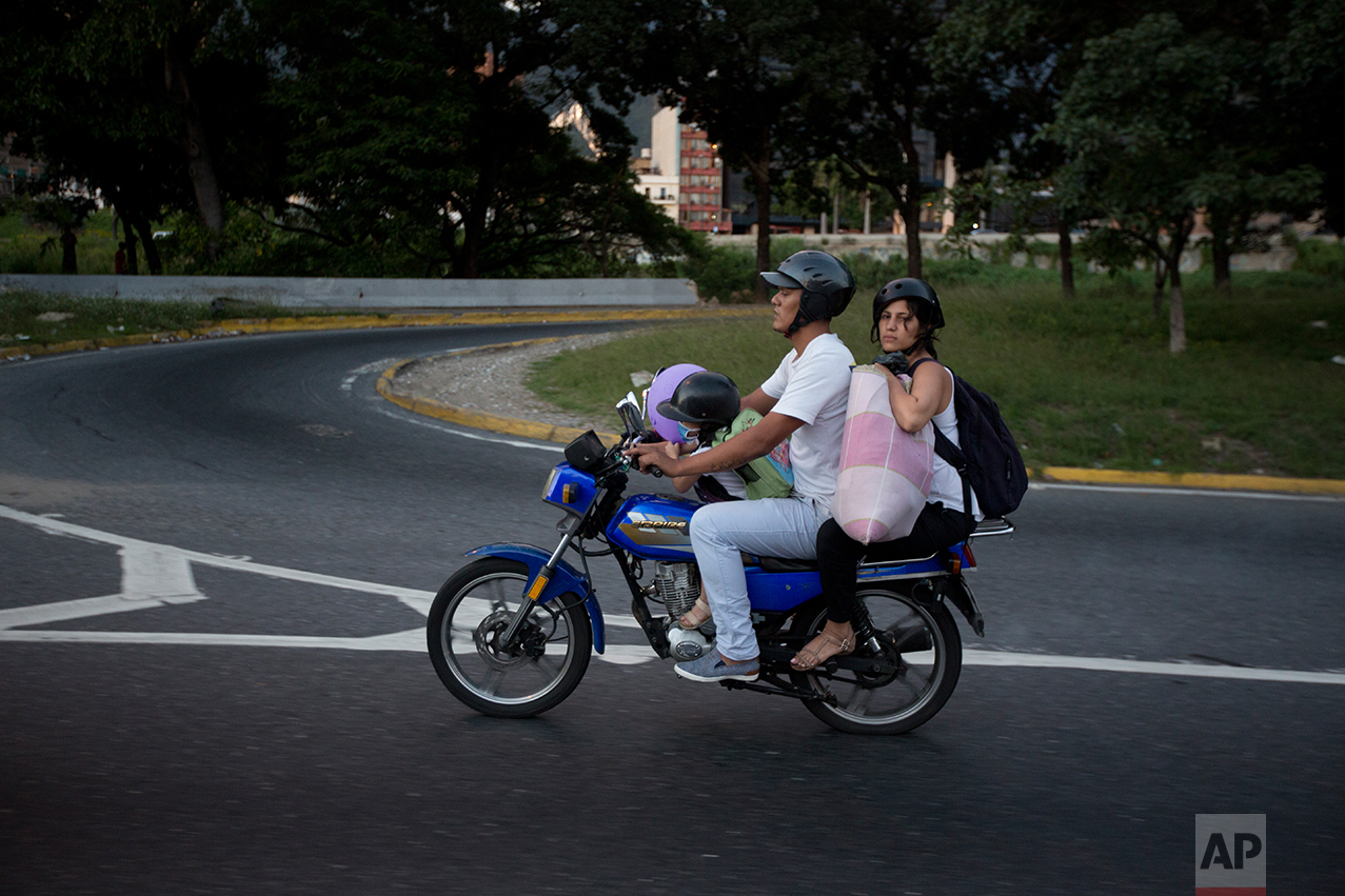 In this Sept. 19, 2016 photo, Maykol Pacheco drives his daughter Ashley, and wife Oriana, away from University Hospital, after a two-month stay, in Caracas, Venezuela. In that time Maykol and Oriana joined the thousands of Venezuelans racing against personal clocks to save loved ones. They stood in hours-long lines outside pharmacies and hospitals just to ask if they had what the doctors needed to care for their child. (AP Photo/Fernando Llano)