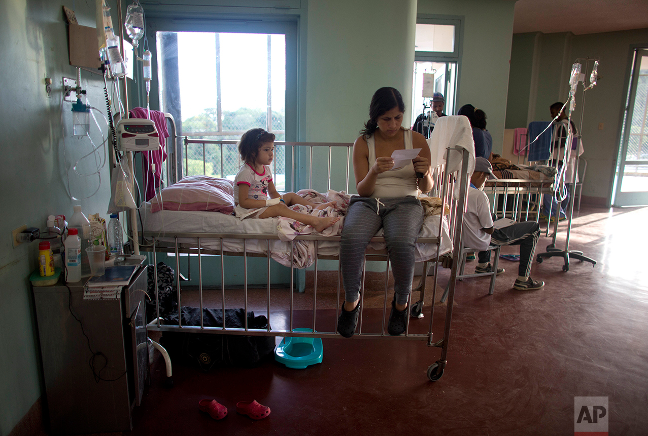 In this Aug. 16, 2016 photo, 3-year-old Ashley sits on her hospital bed as her mother Oriana Pacheco reads a prescription, at University Hospital in Caracas, Venezuela. Ashley's parents not only maxed out their credit cards and borrowed as much money as they could from family to pay for scarce antibiotics, but they were eating just one meal a day, sold their fridge, television, Oriana's cellphone and their children's Play Station. (AP Photo/Ariana Cubillos)