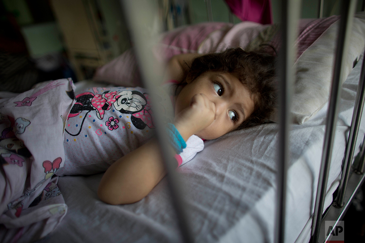 In this Aug. 16, 2016 photo, 3-year-old Ashley Pacheco sucks on her thumb as she rests in a hospital bed during her two-month stay at University Hospital in Caracas, Venezuela. As the health care system collapses, the tiniest slips, like Ashley's tumble while chasing her brother in mid-July, turned into a life-or-death crisis when her scraped knee led to a staph infection. (AP Photo/Ariana Cubillos)