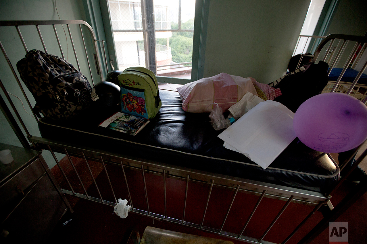 """In this Sept. 19, 2016 photo, the packed belongings of Ashley Pacheco sit on top of her bed, as she waits to be discharged from University Hospital in Caracas, Venezuela. Two months after the 3-year-old was first admitted with a staph infection in her left leg, the doctor declared Ashley infection-free. Her mother sold the medication the family had left over to other mothers on the floor, putting away some of that money for future treatment. """"I could have sold the medicine for four times as much as I did, it's so precious."""" said Pacheco. (AP Photo/Fernando Llano)"""