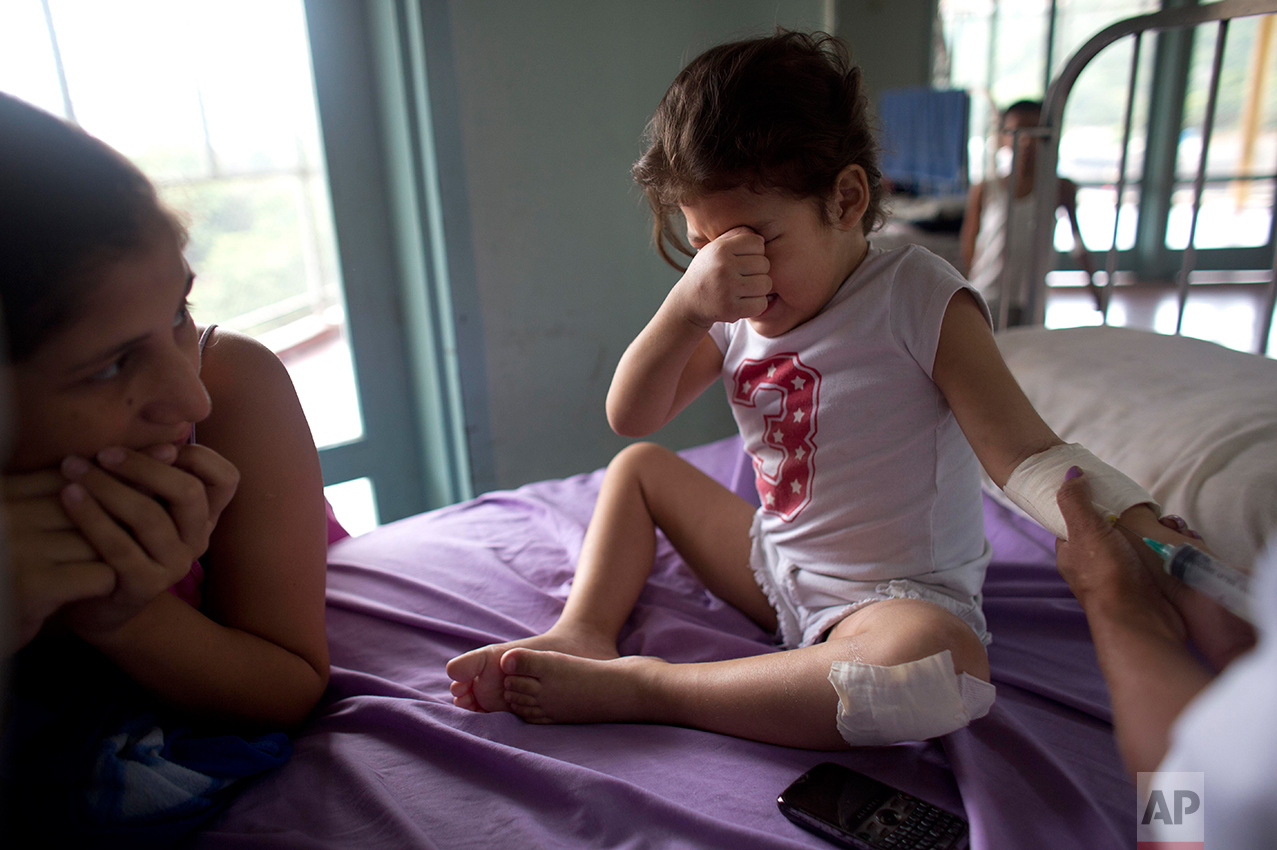 In this Aug. 24, 2016 photo, Ashley Pacheco, 3, cries as she receives an injection as her mother Oriana watches at the University Hospital in Caracas, Venezuela. Two weeks after 3-year-old Ashley scraped her knee, she was screaming in a hospital, fighting for her life as her family scoured Caracas for scarce antibiotics. Venezuela is running short on 85 percent of basic medicines. As the health care system collapses, the tiniest slips, like a little girl's tumble while chasing her brother, are turning into life-or-death crises. (AP Photo/Ariana Cubillos)