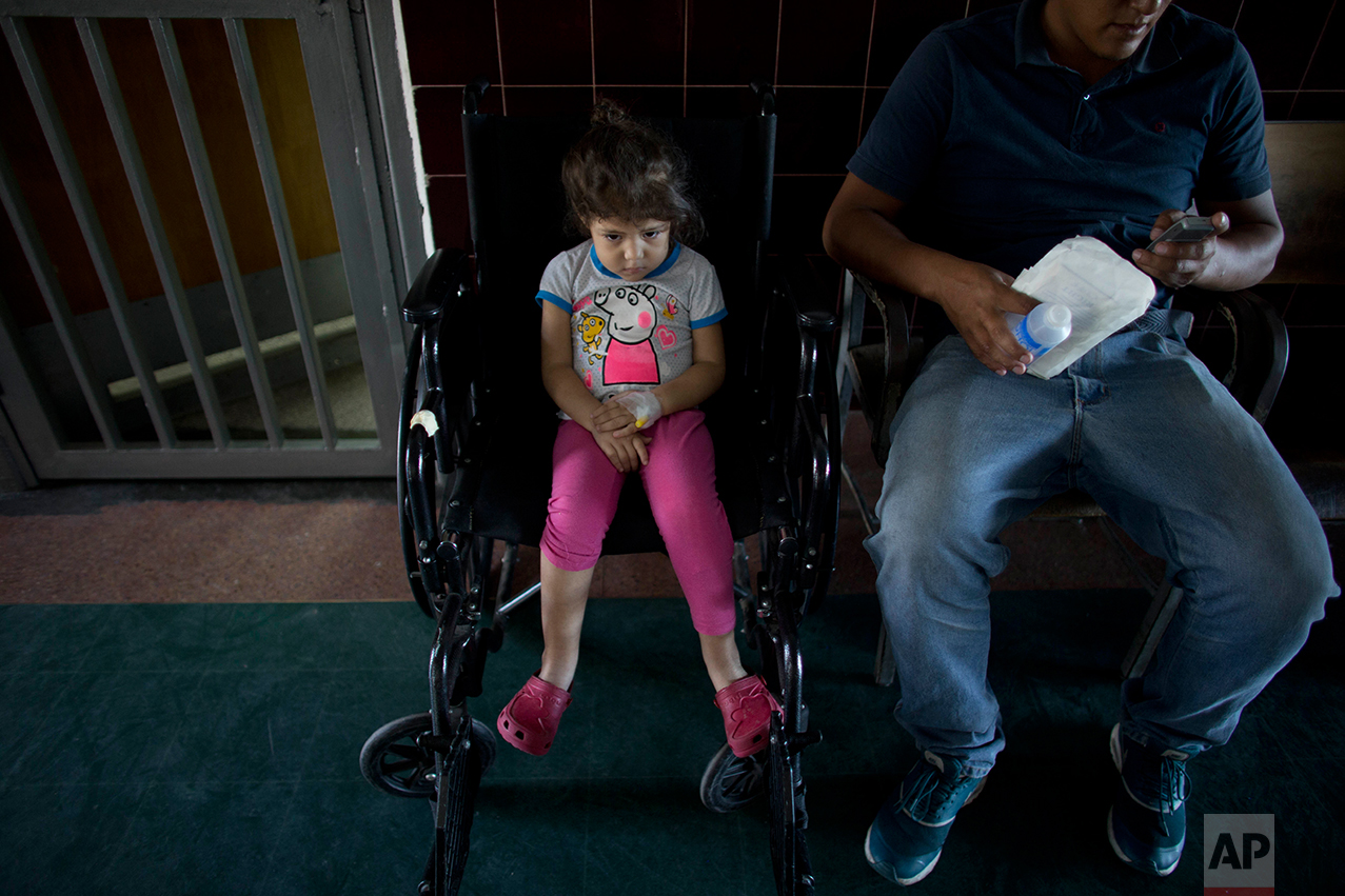 In this Aug. 17, 2016 photo, 3-year old Ashley Pacheco waits with her father Maykol to have her stitches removed from her left leg, at University Hospital in Caracas, Venezuela. Two weeks after Ashley scraped her knee, she was screaming in a hospital, fighting for her life as her family scoured Caracas for scarce antibiotics. When she arrived at the hospital Ashley's left leg had swollen from the tip of her toe to the top of her thigh. (AP Photo/Ariana Cubillos)