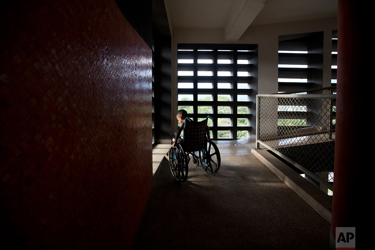 In this Sept. 19, 2016 photo, Marvin Osuna sits near a sunlit window in a passageway at University Hospital, in Caracas, Venezuela. If Venezuela has become dangerous for the healthy, it is now deadly for those who fall ill. One in three people admitted to public hospitals last year died, the government reports. (AP Photo/Fernando Llano)