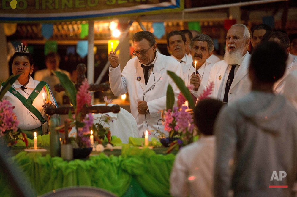 In this June 22, 2016 photo, Godfather Alfredo Gregorio, center, leads a religious service in the church of doctrine of the Holy Daime, in Ceu do Mapia, Amazonas state, Brazil. Alfredo Gregorio de Melo is son of the village founder, rubber tapper Sebastiao Mota de Melo, nicknamed Godfather Sebastiao. (AP Photo/Eraldo Peres)