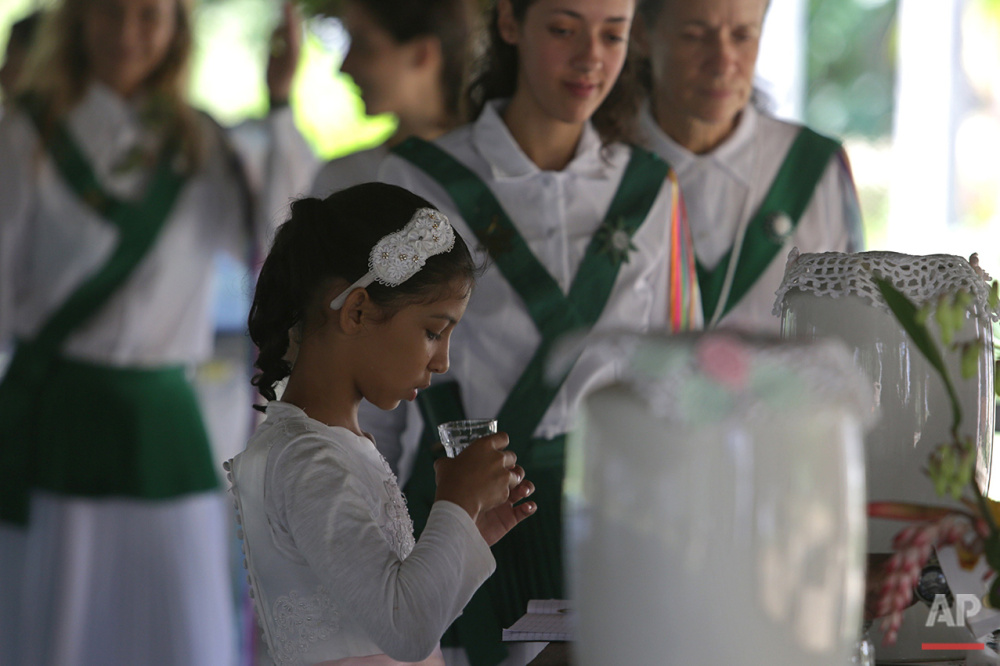 In this June 22, 2016 photo, 9-year-old Natalia Catarina takes part in the consecration of the Holy Daime during a religious service at the church of Ceu do Mapia, in Amazonas state, Brazil. All members of the community, including children, consume the psychedelic tea during the service. (AP Photo/Eraldo Peres)